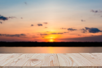 Empty wooden board table top on of blurred sunset and lake background. with copy space for display or montage your products