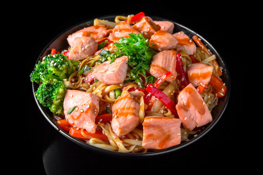 Soba, udon, asian wheat noodles ramen with salmon and vegetables: broccoli, carrots, sweet peppers, zucchini  on a black background. Asian style. Japanese food