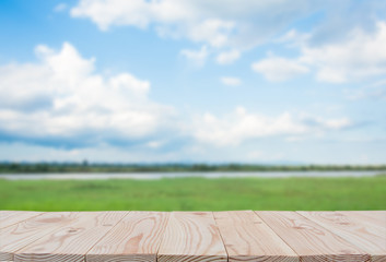 Empty wooden board table top on of blurred blue sky and river  background. with copy space for display or montage your products