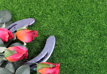 Red silk roses, a horseshoe and artificial green grass for the running of the thoroughbred race called the Kentucky Derby. Copy space