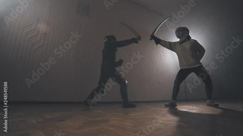 Warriors are fighting during sword battle indoors in slow