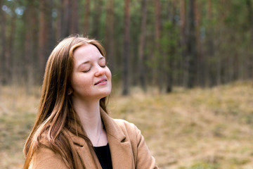 Smilimg dreaming woman with closed eyes in the forest. Positive and growth mindset