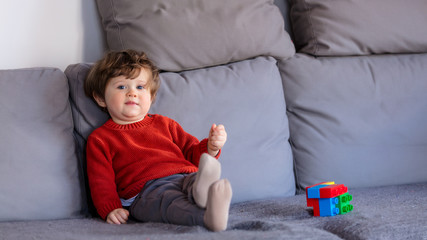 Funny little boy sitting on sofa in red sweater