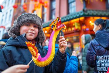Boy holding chinese dragon at new year celebrations, London