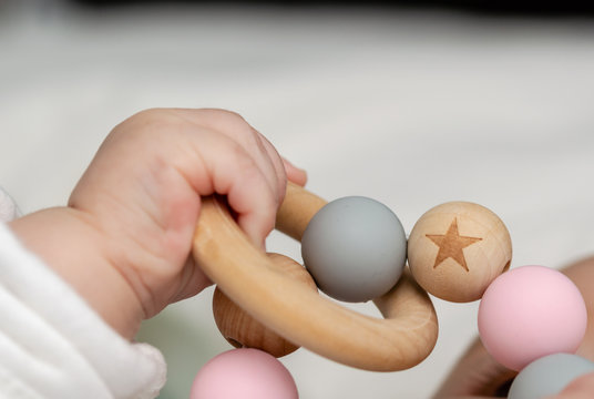 Close-up of a baby´s hand, playing with a wooden toy.