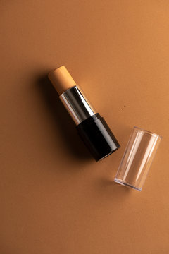 concealer stick, on geometric backgrounds, in shades of brown. Product