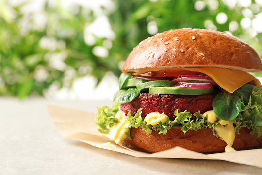 Tasty vegetarian burger with beet cutlet on table against blurred background. Space for text