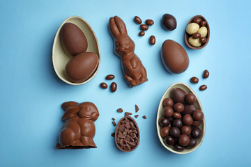 Flat lay composition with chocolate Easter eggs on color background
