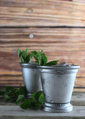 Image for Kentucky Derby in May showing two silver mint julep cups with crushed ice and fresh mint in a rustic setting, vertical, copy space