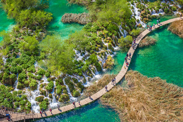 Tourists on the wooden park pathways enjoying the view of emerald lakes, cascades and crystal clear water, Plitvice Lakes National Park, Croatia