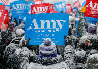 A supporter holds a sign in the snow during Klobuchar rally in Minneapolis