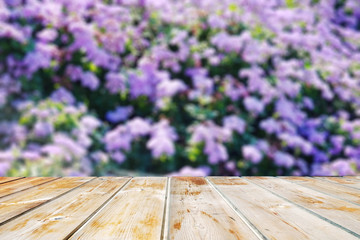 Wood table top on blur violet flower garden background - can be used for display or montage your products.