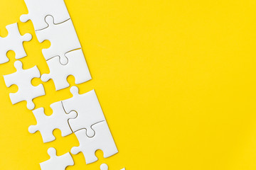 White jigsaw puzzle on vivid yellow background with copy space using for thinking strategy for business solution, teamwork, connection or idea for success