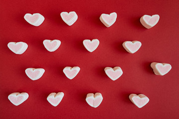 Marshmallow in the form of hearts on red background. Valentine's Day.