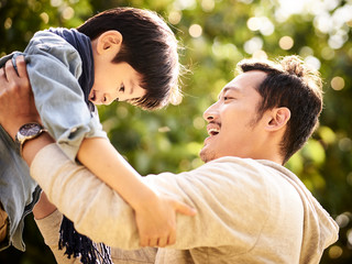 asian father lifting child son in joy