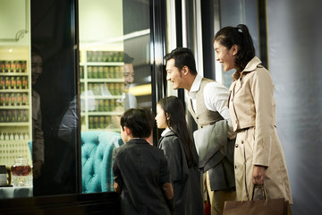 asian family looking into shop window