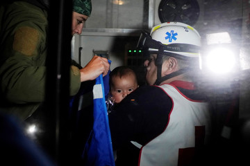 A child, rescued from Rio Bravo together with a group of migrants from Honduras while trying to cross towards the United States, is held by a paramedic inside an ambulance in Piedras Negras, Mexico
