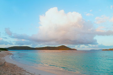 Fototapete - A huge cumulus cloud over sandy beach on tropical island at sunset. Beautiful tranquil landscape of mountainous Virgin Islands on horizon.