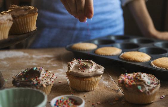 Hand adding sprinkles to chocolate cupcake food photography recipe idea