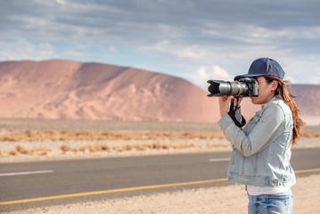 Woman photographer taking photo in the desert