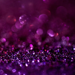 Purple glitter magic background. Defocused light and free focused place for your design.