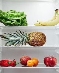 Open refrigerator containing fresh and healthy foods.