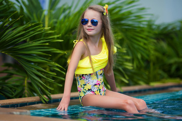 Cute girl in sunglasses in the swimming pool outdoors