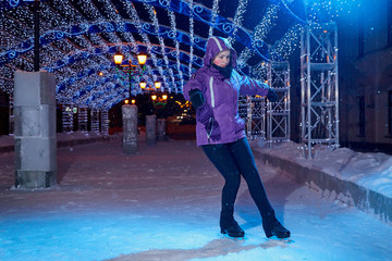 Girl skating on the ice arena in the evening city square in winter