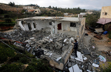 Palestinian man takes pictures of a house after it was demolished by Israeli forces in the village of Al-Walaja near Bethlehem, in the Israeli-occupied West Bank