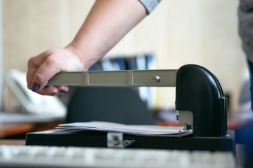 Office worker is punching a paper sheets with hole puncher. Paperwork background.