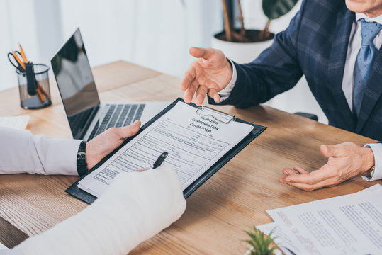 cropped view of worker with broken arm signing form for compensation claim  opposite to businessman in blue jacket in office, compensation concept