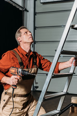 repairman in orange uniform climbing with screwdriver on ladder in garage