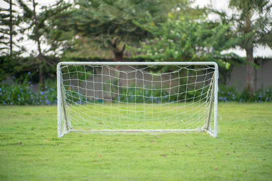 Selective focus on a small soccer goal with rope net puts on the grass field with blurred garden and trees in background