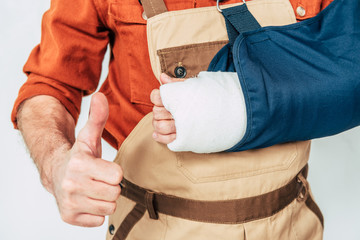 cropped view of repairman with arm bandage showing thumb up on white background