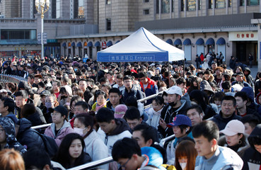 Passengers wait to enter a subway outside Beijing Railway Station as the annual Spring Festival holidays end in Beijing
