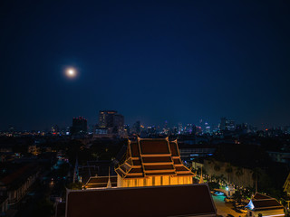 Bangkok Cityscape and Full moon sky view from golden mount at wat saket temple Thailand.The landmark travel destination of bangkok city thailand