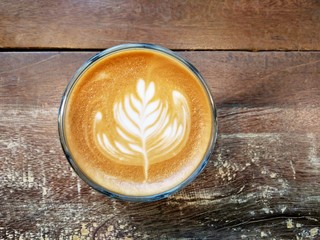 Cup of coffee on the table with latte art - Rosetta, top view on wooden table background.