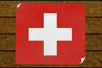 Illustration of a Swiss flag on the paper pasted on the woody wall