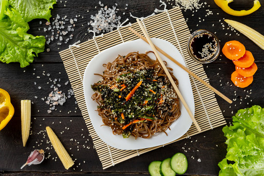 Flatlay plate of buckwheat noodles with vegetables salad served with chopsticks at decorated wooden table background.