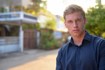 Face of young handsome businessman with blond hair outdoors