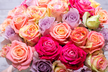 Beautiful bouquet of roses in a gift box. Bouquet of pink roses. Pink roses close-up. on wooden background, with space for text.