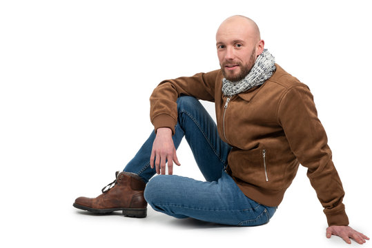 young man with a beard sitting on the ground on white background