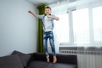 The boy jumps on the couch in the living room, having fun, fooling around, while his parents are not at home. Baby sitting, baby alone at home.