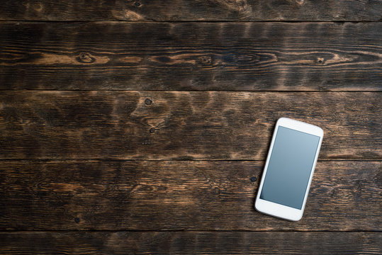 Blank screen mobile phone on a brown wooden board background with copy space.