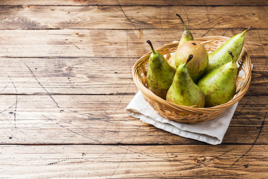 Fresh juicy Pears Conference in a basket on a wooden rustic background.
