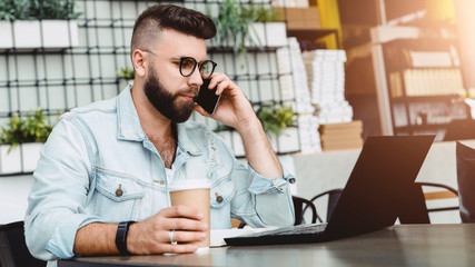 Young smiling bearded man having mobile phone conversation with business partner, while sitting with laptop in cafe.