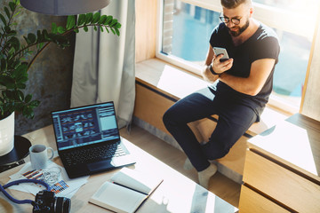Attractive hipster guy sits home on windowsill, reads text messages, sends e-mail, browses social networks, uses his smartphone and fast internet connection. On table is laptop, camera, paper notebook