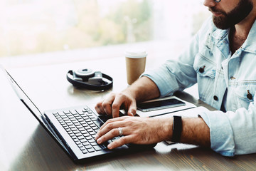 Closeup of male hands typing on computer keyboard. Bearded man uses laptop in cafe while sitting at table. Businessman working remotely.Young man works on mobile device. Blurred window background.