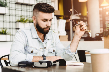 Portrait of young bearded male writer. Guy sits with notebook in cafe at table, holds pencil in his hand and reads book. Journalist writes article for newspaper. Student doing homework, reads synopsis