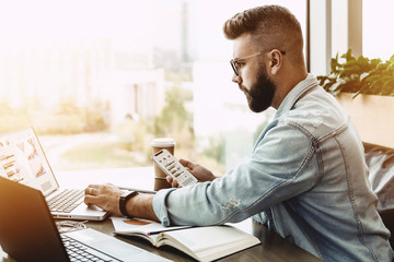 Hipster man sits in cafe, holding smartphone, works on laptop with charts, graphs, diagrams on screen. Businessman checks information on phone. On table is notebook, paper documents. Online marketing.